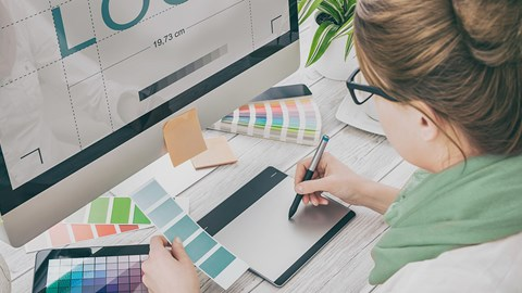 Female sitting at a computer designing a logo surrounded with colour charts and ideas