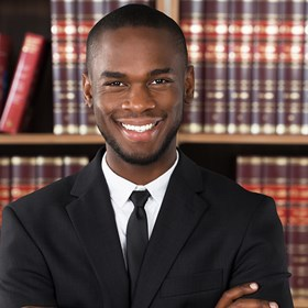 Young male lawyer standing in front of book case