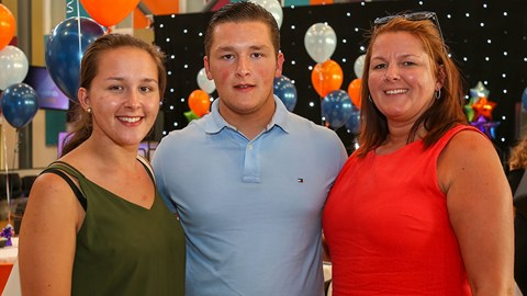 Male student with sister and mum either side at student awards