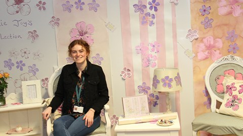 Professional (vocational) student sitting in a interior design set she created, including a chair, hand designed wallpaper and a table