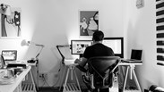 black and white image of a man working in a home office with two sceens