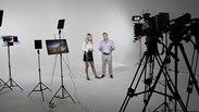 film studio with two presenters surrounded by microphones, cameras and screens